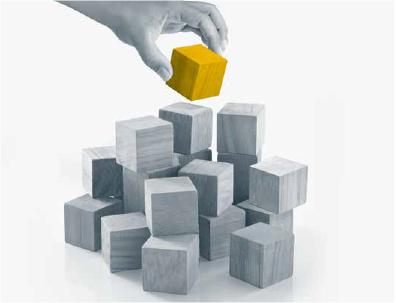 Foto i gråblå toner av byggeklosser i tre på en hvit, nøytral bakgrunn. Det er omtrent fire i bredden og tre i høyden, plassert hulter til bulter. Øverst i bildet er det en menneskehånd i gråblå toner som holder en byggekloss. Byggeklossen hånden holder er i en sterk okergul farge.