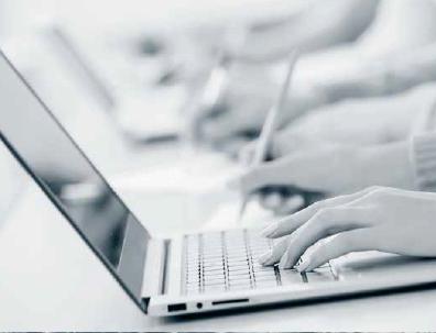 Foto fra siden av en bærbar PC. Vi ser to hender som arbeider på PC-en. Bildet er i gråtoner. I bakgrunnen skimter vi en rad med flere PC-er, men disse er uskarpe.